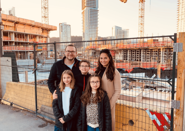 Marko and his family standing in front of the construction fence at the Coquitlam YMCA construction site